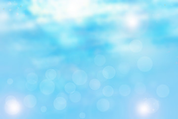 Blurred blue sunny and white bokeh backround with bright shining clouds as well as natural sky. Abstract background.