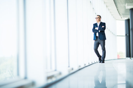 Senior businessman looking out a window in modern office