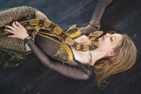 Young female dancer lying on the floor with a snake on her body