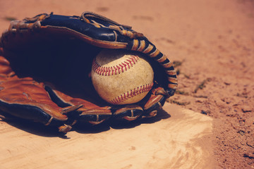 Vintage baseball in players glove laying on homeplate, ball field dirt in background.