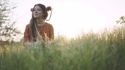 beautiful hippie woman with dreadlocks in the woods at sunset having good time outdoors