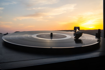Turntable vinyl record player on the background of a sunset over the mountains. Sound technology for DJ to mix & play music. Black vinyl record. Vintage vinyl record player.