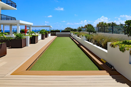 Inviting upscale bocce ball court with artificial turf, on a rooftop terrace.