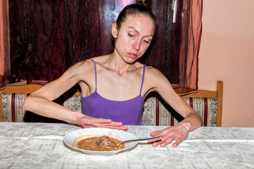 Young skinny anorexic girl with anorexia refusing to eat
