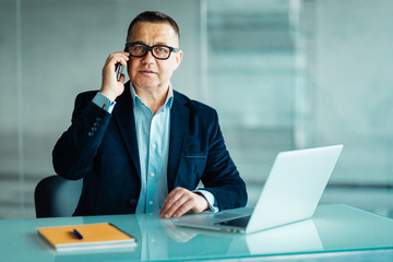 Middle aged businessman with laptop talking on phone in modern office