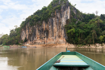 Boat on the Mekong River in front of a limestone cliff where the famous Pak Ou Caves are set. They are located near Luang Prabang in Laos.