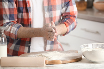 Man sprinkling flour over board on table in kitchen