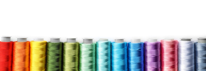 Color sewing threads on white background, top view