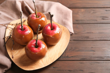 Plate with delicious caramel apples on wooden background