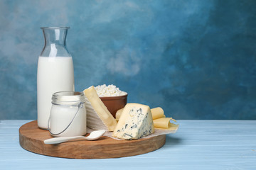 Fresh dairy products on table against color background