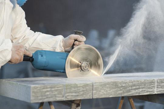 Worker cuts stone grinding machine