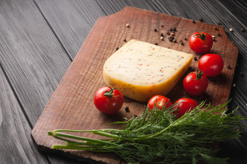 Cheese on a brown wooden board on a black wooden background, cherry tomatoes, pepper, greens, spices, dill, parsley. View from above.