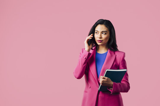 Portrait of a young woman in pink suit talking on the phone and holding folder, isolated on pink studio background