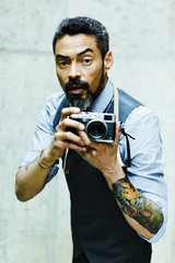 Portrait of a photographer with tattoo and beard taking photos