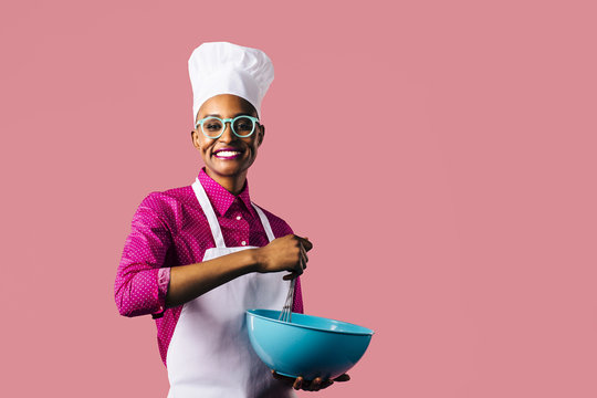 Portrait of a very happy and smiling young woman in cooking hat and apron mixing a bowl with a whisker, isolated on pink studio background