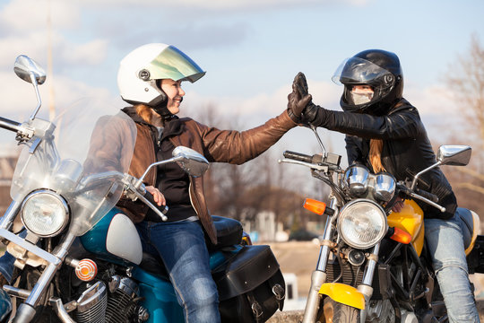 Clapping hands in leather gloves while greeting each other on urban road in partnership