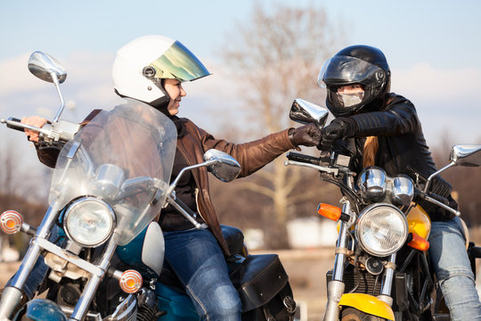 Two women bikers greeting each other with fists blow, usually gesture of motorcyclists