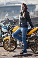 Young woman biker wearing neck face mask posing behind her street bike outdoor