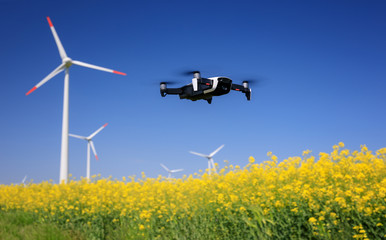 Inspection drone with eolian turbines behind. Rapeseed field in bloom. Renewable energy. Wall mural