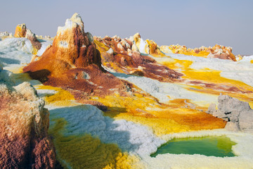 Yellow sulfuric volcanoes emitting toxic gas clouds, sulfur deposits white and green colors Danakil desert, Afar basin in the north of Ethiopia.