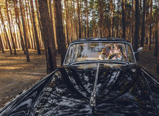 Young wedding couple sitting smiling inside retro car and looking at each other view through the window clouse-up. just married embrace hugging inside car. bride hugging groom. Wedding with retro car