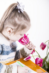 Little girl sniffing tulips, draws a greeting card to mum. Many multi-colored pencils on the orange table in the nursery