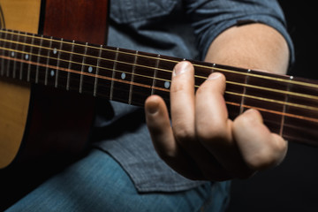 male hands play acoustic guitar