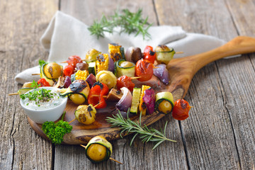Vegetarisch grillen: Bunte  Gemüsespieße vom Grill mit Kräuterdip  - Grilled skewers with mixed vegetables served  on a wooden cutting board with a vegan herb dip