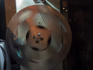 Spinning film reel in a dark room projecting a film