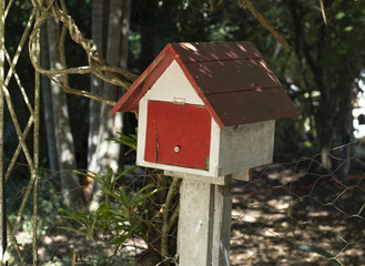 Painted wooden mail house white and red in the driveway