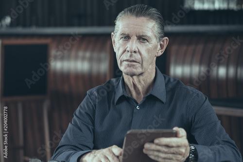 Thoughtful Senior Businessman Looking At Camera Sitting At
