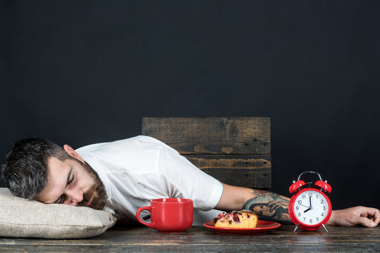 Bearded man sleeping at table on pillow with alarm clock and cup of coffee on kitchen. Exhausted man resting. Tired businessman sleeping at home. Very tired man sleep at table after long hours at work