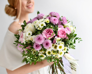 Beautiful woman hold bouquet of chrysanthemum and roses flowers white and purple happy smiling on grey