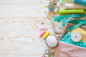 Many different rainbow materials for needlework and sewing. A girl / woman is drinking tea.