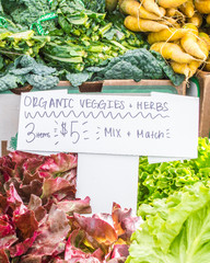 colorful vegetables and herbs with hand written sign at a farmer's market