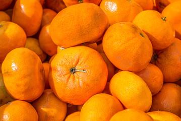 full frame close up of bright orange ripe tangerines at a farmer's market