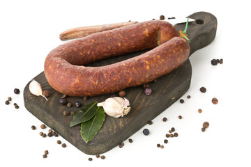 German specialty salami hard cured sausage whole with spices on wooden board