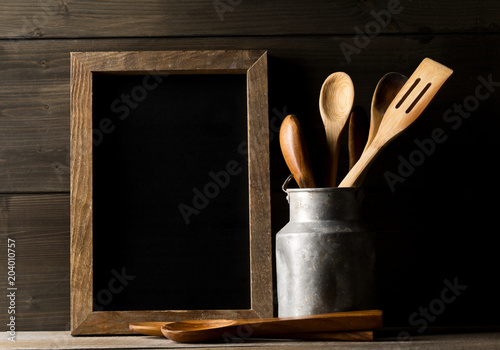 Wooden Kitchen Cooking Tools With Spoons And Spatula Menu Board In Front Of Rustic