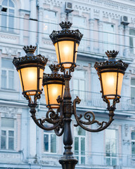group of bright street lamps on a column illuminating a street in the background of a building