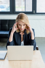 high angle view of concentrated businesswoman using laptop at workplace