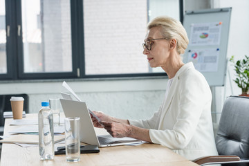 side view of attractive senior businesswoman in eyeglasses reading documents in office