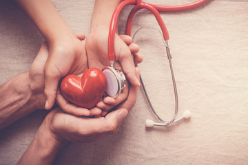Fototapeta child and adult holding red heart with stethoscope, heart health,  health insurance concept, world heart day, world health day, world hypertension day, health insurance obraz