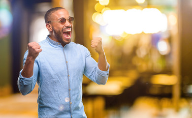 African american man with beard happy and excited expressing winning gesture. Successful and celebrating victory, triumphant at night