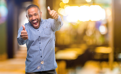 African american man with beard stand happy and positive with thumbs up approving with a big smile expressing okay gesture at night