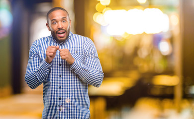 African american man with beard happy and surprised cheering expressing wow gesture at night