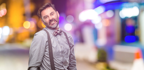 Middle age man, with beard and bow tie angry and stressful frowns face in dissatisfaction, irritated and annoyed, expressing anger at night club