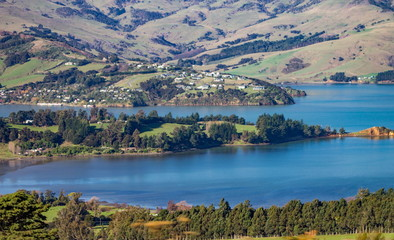 Landscape view of the rolling hills and harbour of Akaroa, Banks Peninsular, New Zealand.