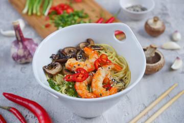 Hot asian wok noodles with shrimps and mushrooms, Preparation ramen, Gray background, Closeup