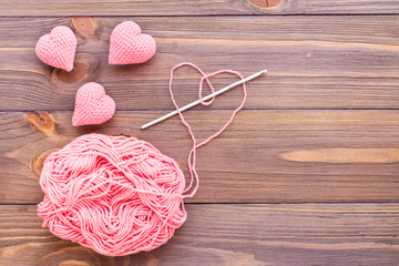Knitted pink hearts, tangle of thread and needle on a wooden background. Top view