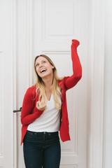 Cheerful blonde woman raising hand against door
